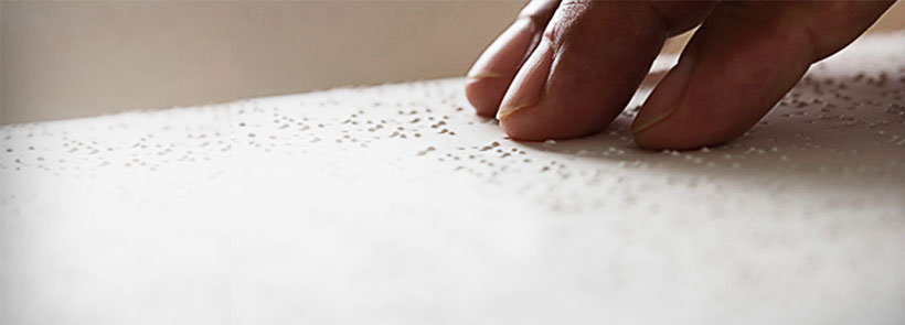 Image of hand scanning braille.